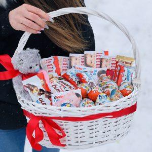 Мягкая игрушка и шоколадные сладости в корзине